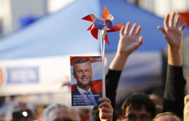 A supporter holds a picture of Austrian FPOe presidential candidate Hofer during his final election rally in Vienna